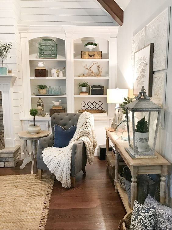 Living room scene with accent chair covered with blanket and pillow, side table styled with large lantern, wall shelves