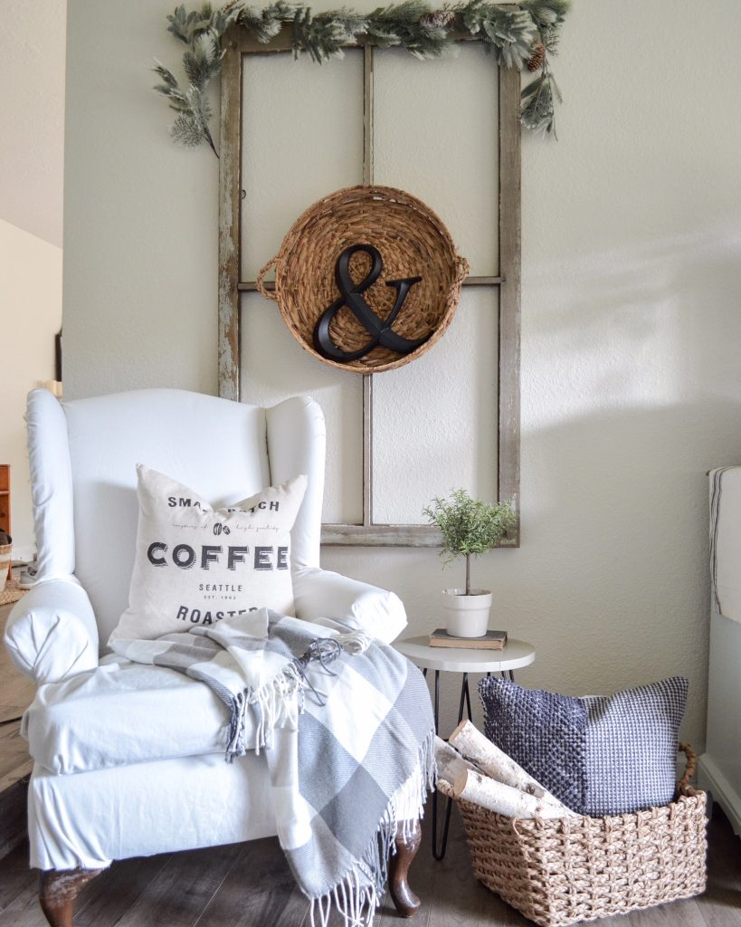 Rustic window pane in living room with garland and basket on it, accent chair with pillow and buffalo check blanket, woven basket with birch logs and pillows