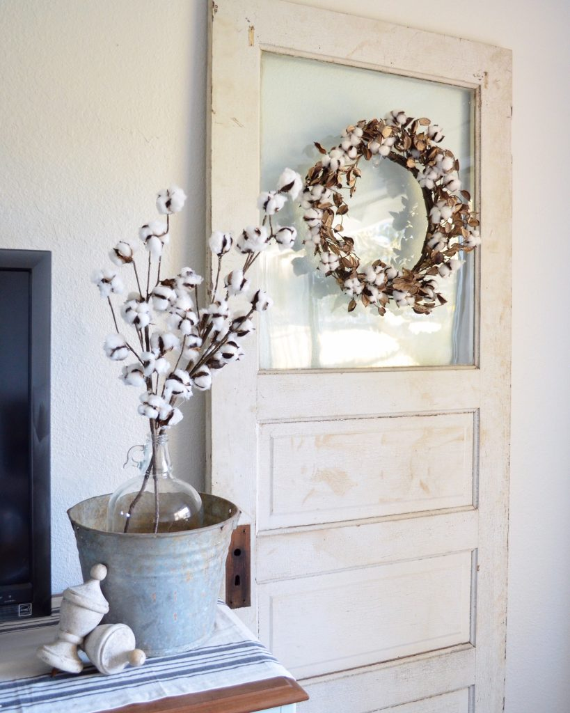 Cotton stems in galvanized bucket on table with cotton stem wreath on open door