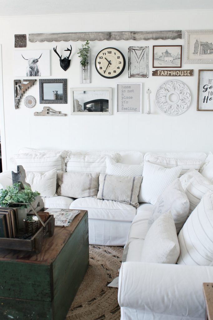 Winter white corner couch with neutral colored gallery wall behind