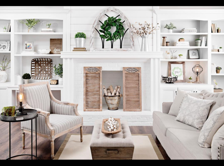 Cozy winter white living room with mantle and side shelved styled in winter farmhouse style