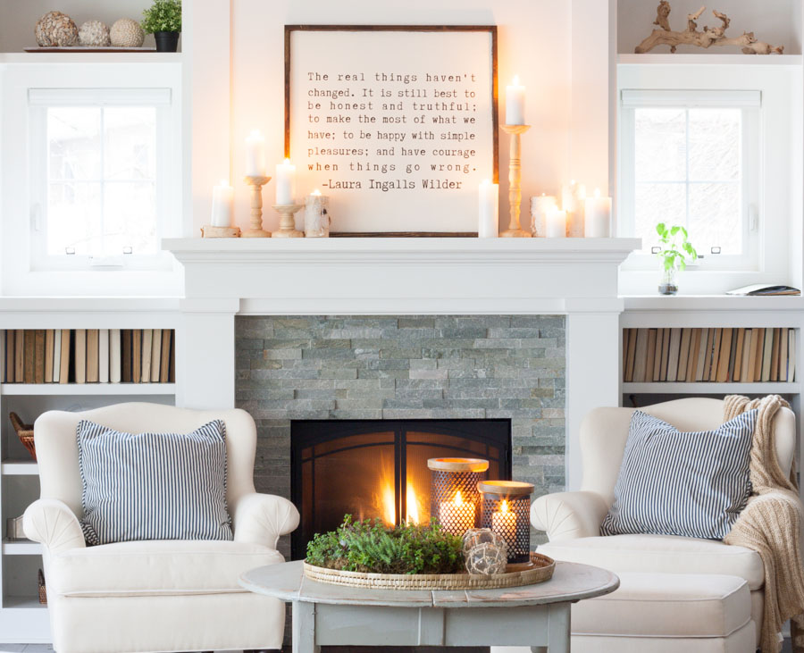 Cozy living room with neutral chunky candle holder with white candles, laura ingalls wilder quote print on top, with accent chairs and table in front of fire place