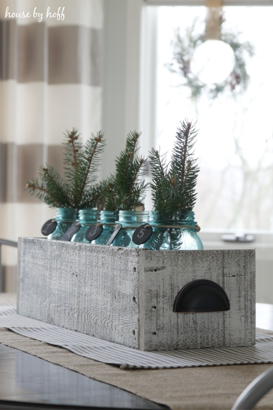 Rustic crate on table filled with mason jars and pine greens