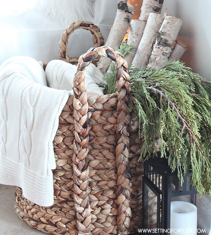 Birch logs and evergreen branches and blanket in woven basket next to lantern with candle