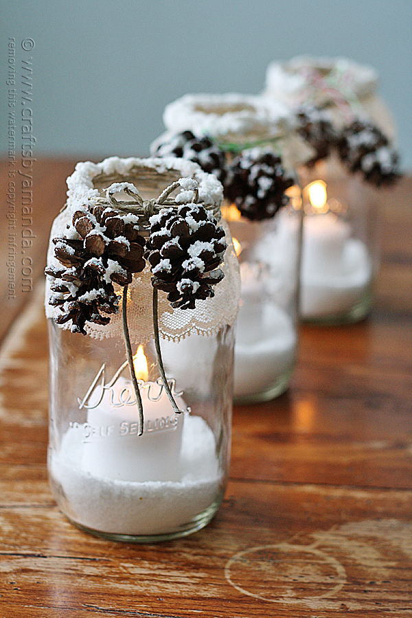 Mason jars with faux snow at bottom, votive inside with pinecones and lace around the tops