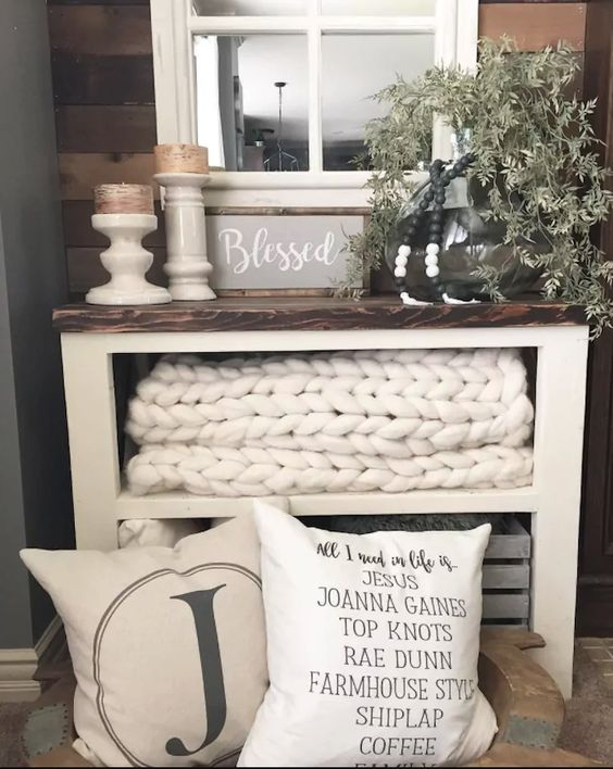 End table with neutral colored pillows in front, chunky knit blanket on shelf, chunky candleholders with candles, greens in a glass gar, beads, and farmhouse sign