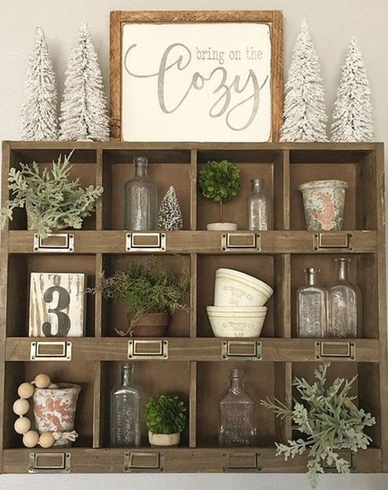 Rustic apothecary shelf with bottlebrush trees, glass bottles, rustic chippy planters, farmhouse signs, and greens
