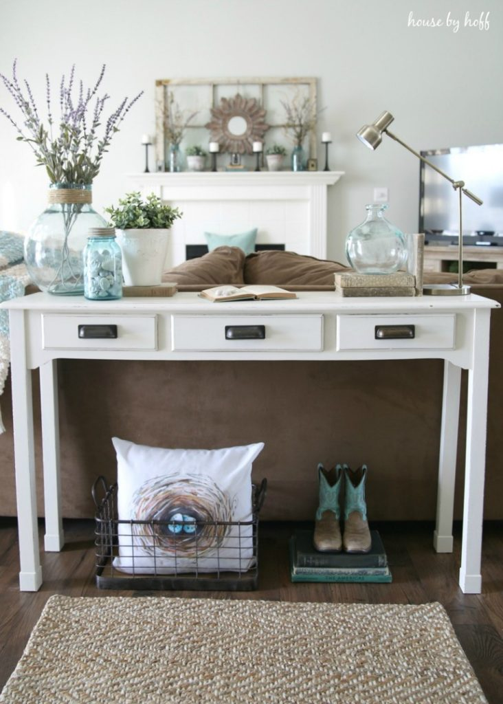 White console table with glass jars filled with rocks, blooming branches with books on top and basket and pillows below,