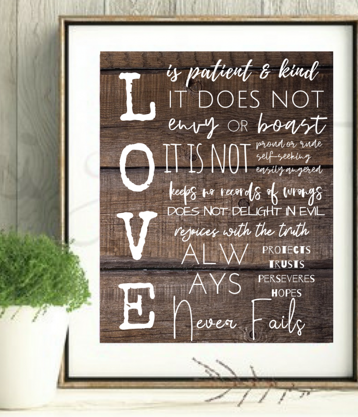 love is patient and kind wall art printable, white letters against dark wood in frame with styled with plant