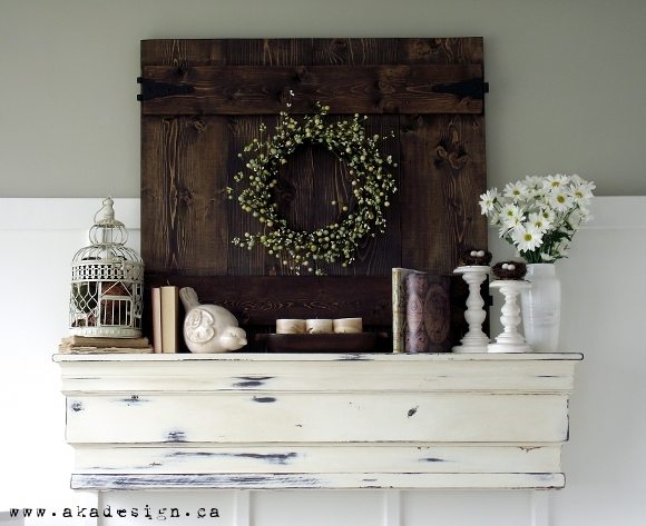 Distressed white mantel with dark stained shutter and wreath, with white flowers, candlesticks and decorative pieces, perfect ideas for rustic farmhouse spring home decor