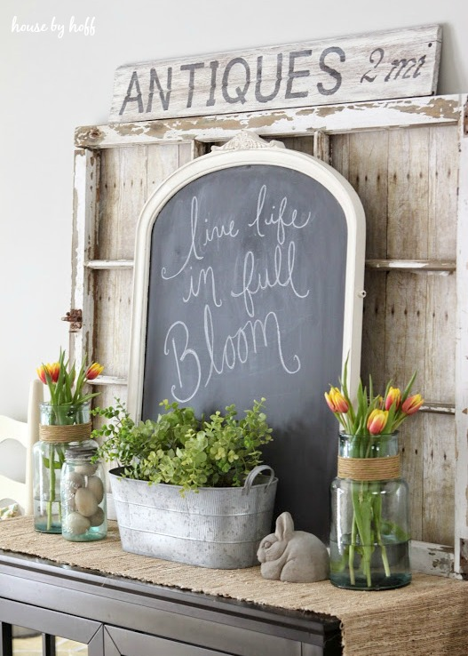 Spring rustic tabletop with rustic chalkboard, tulips in jars with jute spring, galvanized planted with greens, rustic window, perfect ideas for rustic farmhouse spring home decor