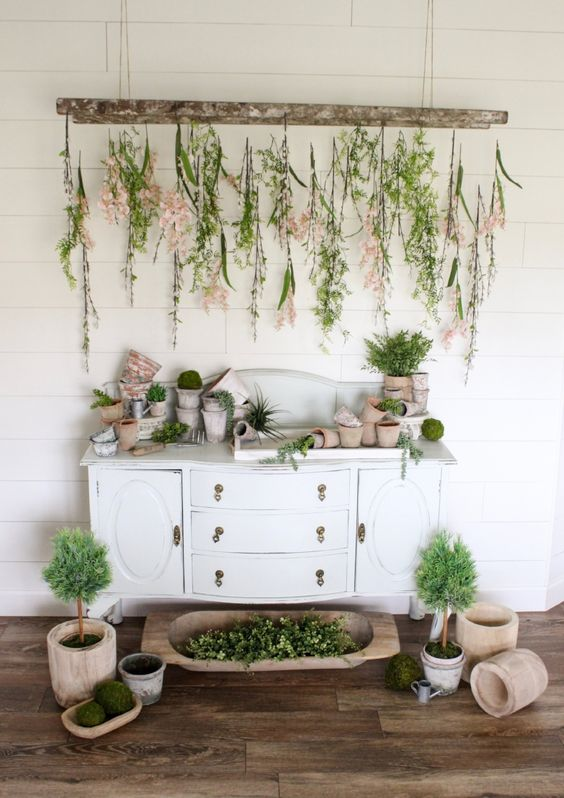 Buffet table with hanging branches of flowers, empty terra cotta pots displayed on table with terra cotta planters on floor, perfect ideas for rustic farmhouse spring home decor