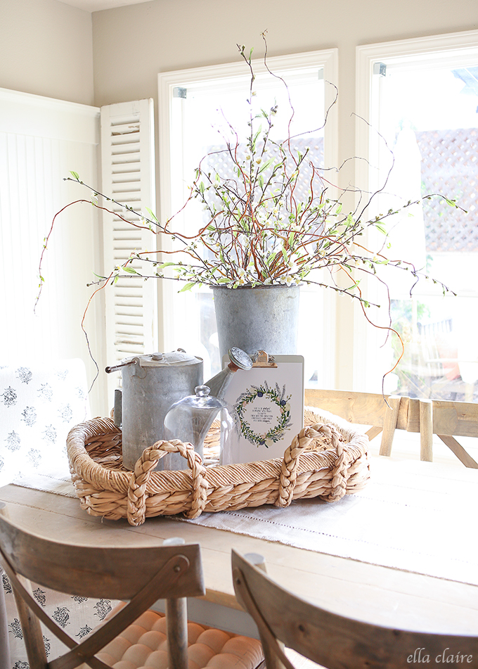 Woven basket filled with galvanized pails and buckets with blooming branches on kitchen tabletop, perfect ideas for rustic farmhouse spring home decor