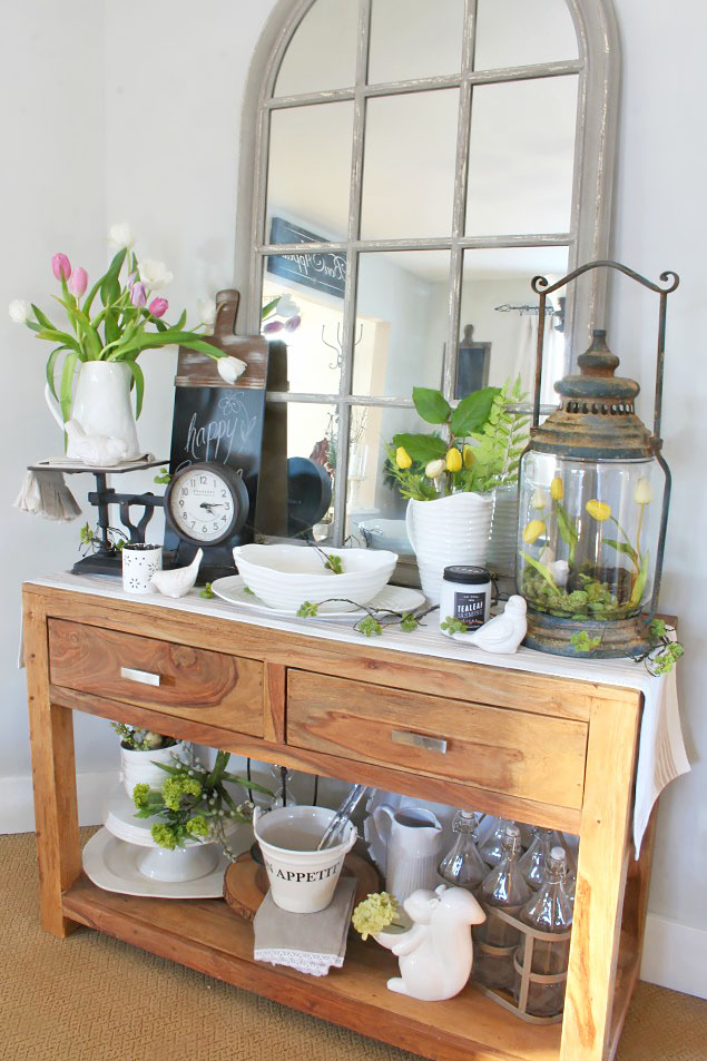 Console table with window pane mirror with tulips in white pitchers, planters, and glass terrarium jar, perfect ideas for rustic farmhouse spring home decor