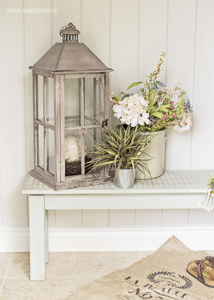 Entryway bench with rustic, distressed lantern, ceramic planter with hydrangeas and wildflowers, perfect ideas for rustic farmhouse spring home decor