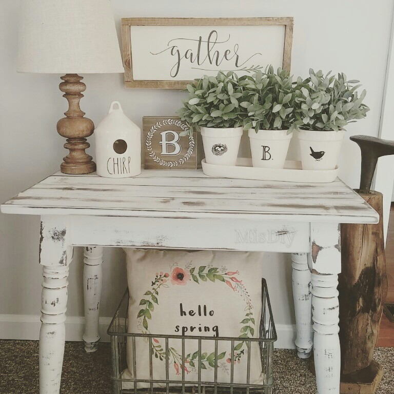 "Distressed table with white painted terra cotta pots with greens, and wooden and white signs and and lamb, with ""Hello Spring' pillow in wire basket below, perfect ideas for rustic farmhouse spring home decor"