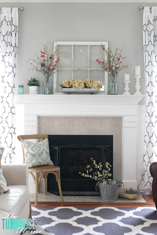 Repurposed window on mantel with glass jars of flowers and white candle sticks, perfect ideas for rustic farmhouse spring home decor