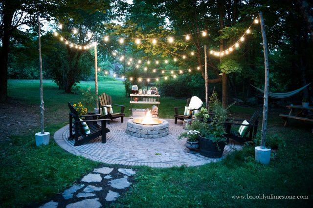 firepit with adirondack chairs with white string lights