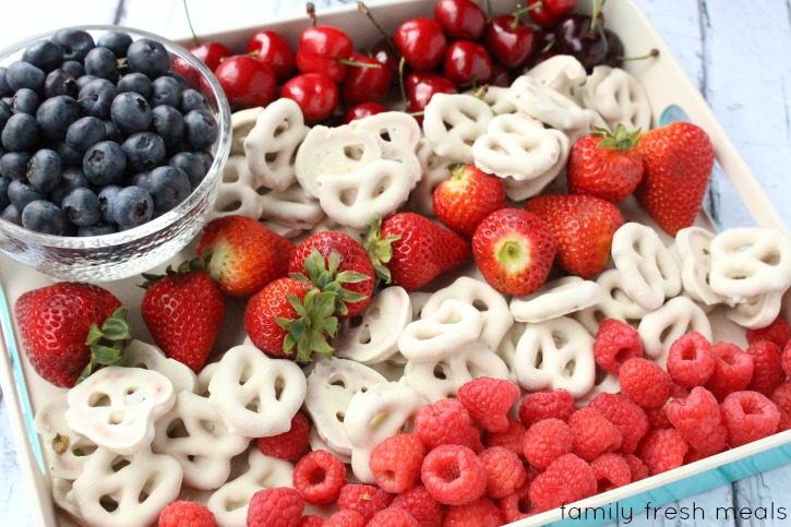 Patriotic Flag Fruit Dessert - bowl of blueberries with alternating rows of cherries, strawberries, raspberries with white yogurt-covered pretzels in between to create an American flag pattern