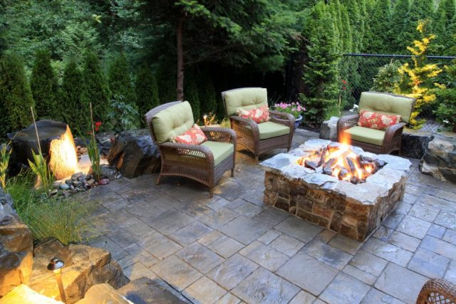 Outdoor tiled patio with green cushion armchairs around fire pit