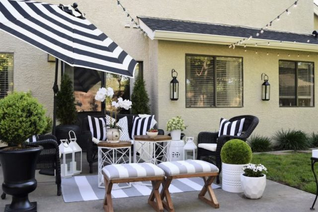summer backyard patio lounge area- black and white striped umbrella and cushions