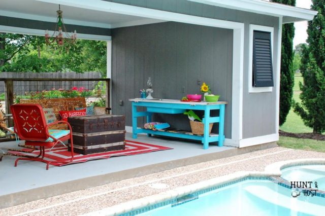 Colorful summer poolside backyard - red chair, aqua table, cabana