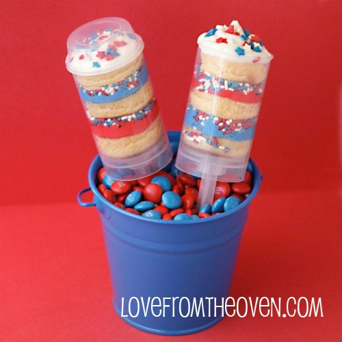 Patriotic Push Pop - push pops with layers of red and blue frosting with sprinkles and yellow cake topped with white whipped cream and red, white blue sprinkles, in blue pail filled with red and blue M&Ms