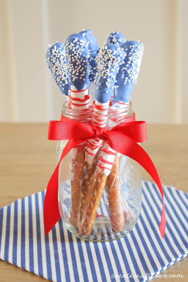 4th of July Dipped Pretzels -pretzel sticks dipped in white and blue chocolate with red icing wrapped around with white sprinkles. In a mason jar with a red ribbon