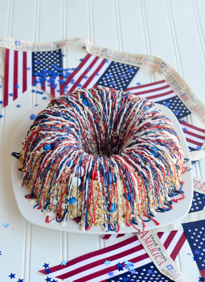 Red White Blue Krispie Bundt Cake drizzled with red, white blue chocolate striped with red, white, blue candies and M&Ms