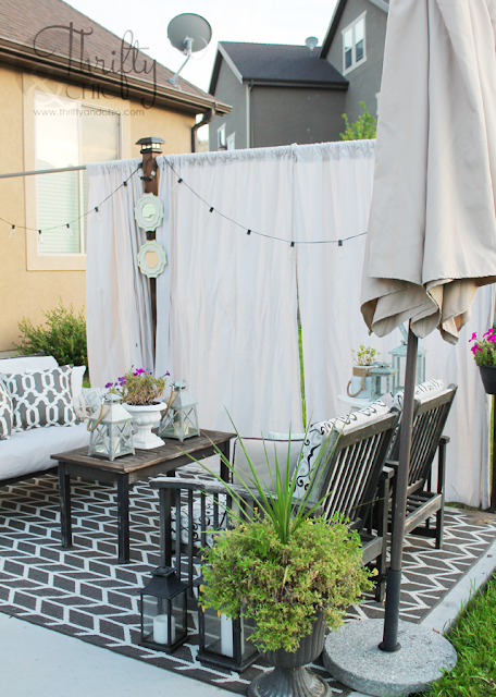 summer backyard patio with couch, coffee table chairs with privacy curtains and string lights