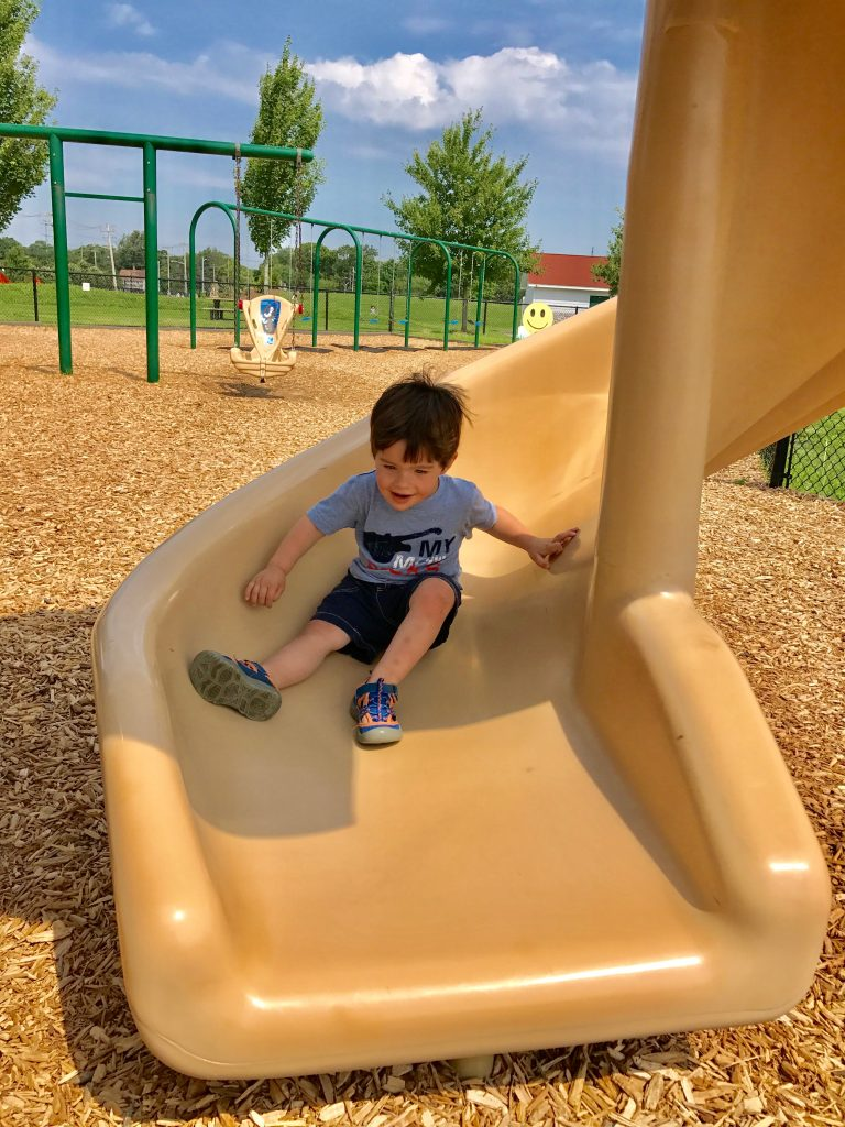 Little boy on slide - Are you already counting down the days the kids go back to school? Has the summer crazy with the kids wearing you out all ready? Keep reading for 5 ways you can hit a reset after a rough day and end the day on a high note! #parenting #kids #familytime #summer #NeverFlySolo #RedBaronPizza #sponsored