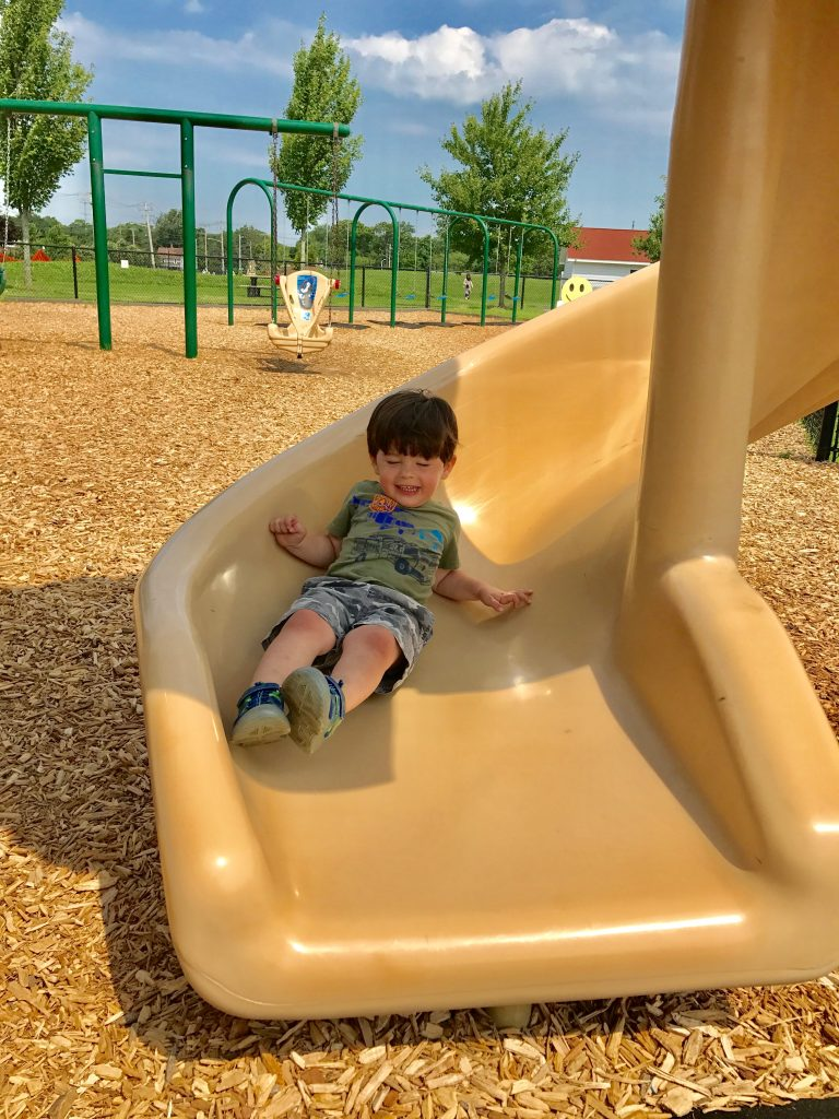 Little boy on slide- Are you already counting down the days the kids go back to school? Has the summer crazy with the kids wearing you out all ready? Keep reading for 5 ways you can hit a reset after a rough day and end the day on a high note! #parenting #kids #familytime #summer #NeverFlySolo #RedBaronPizza #sponsored