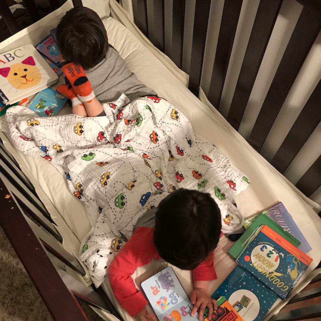 Boys reading books in crib - Are you already counting down the days the kids go back to school? Has the summer crazy with the kids wearing you out all ready? Keep reading for 5 ways you can hit a reset after a rough day and end the day on a high note! #parenting #kids #familytime #summer #NeverFlySolo #RedBaronPizza #sponsored