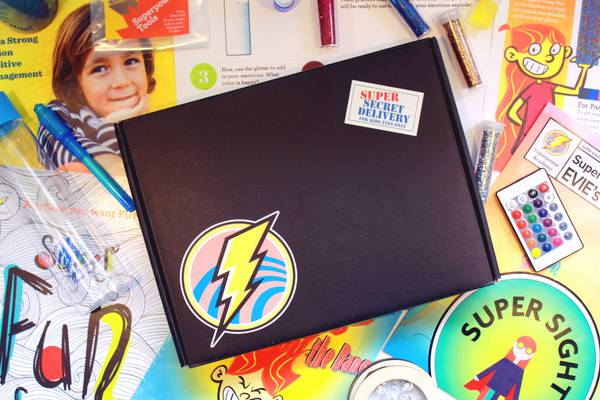 Superpower Academy Subscription box for kids 5-10, displayed with superhero props, cards, and activities