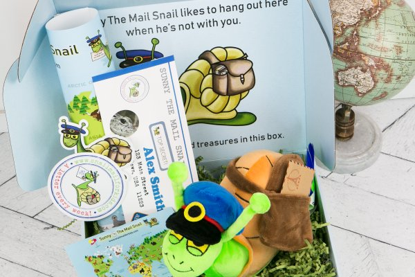 Snail Mail for Kids Subscription box displayed with Mail Snail book , stuffed animal ,travel ticket and props