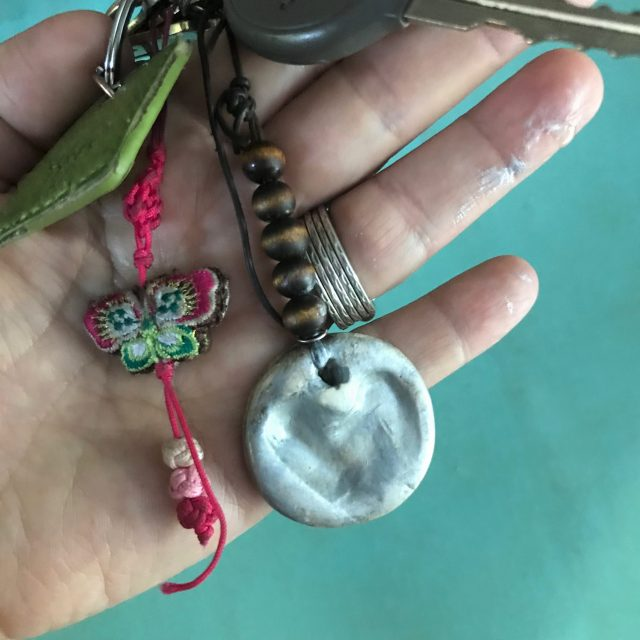 Close up DIY clay thumbprint keychain with butterfly keychain on hand