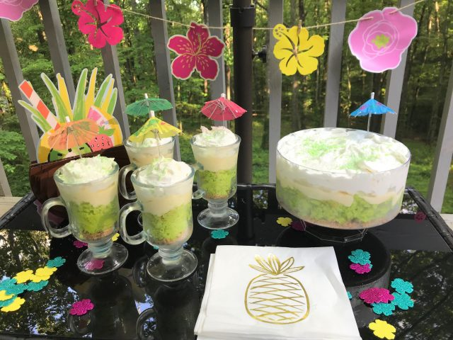 party setting of key lime coconut parfaits and trifle with pineapple napkin and luau flowers