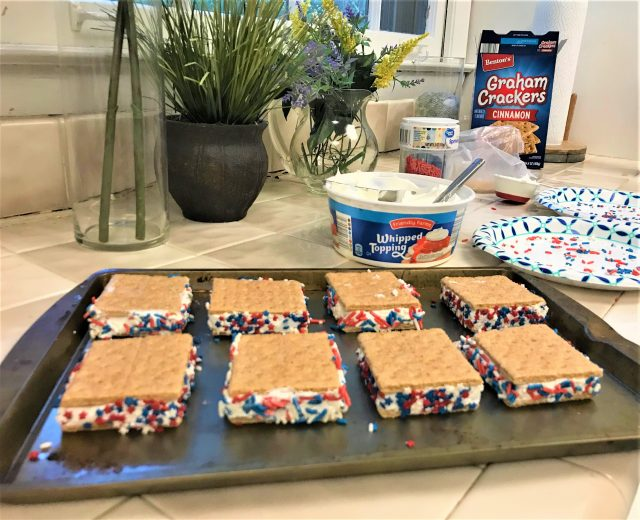 red white blue graham cracker sandwiches on cookie sheet with cool whip and sprinkle ingredients