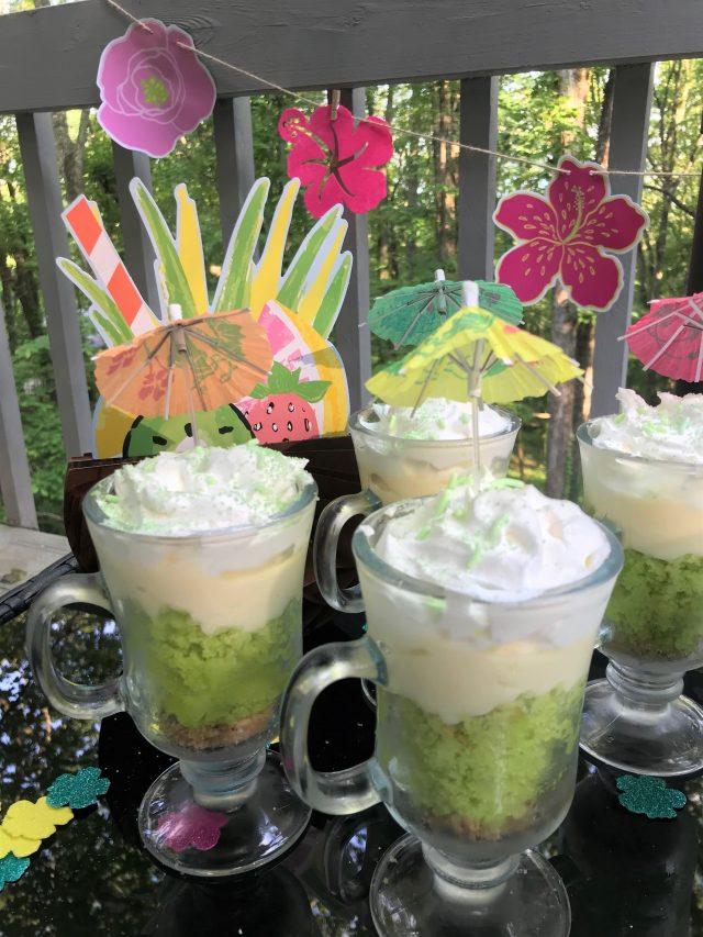 Close up key lime coconut parfaits with luau flowers and decorations
