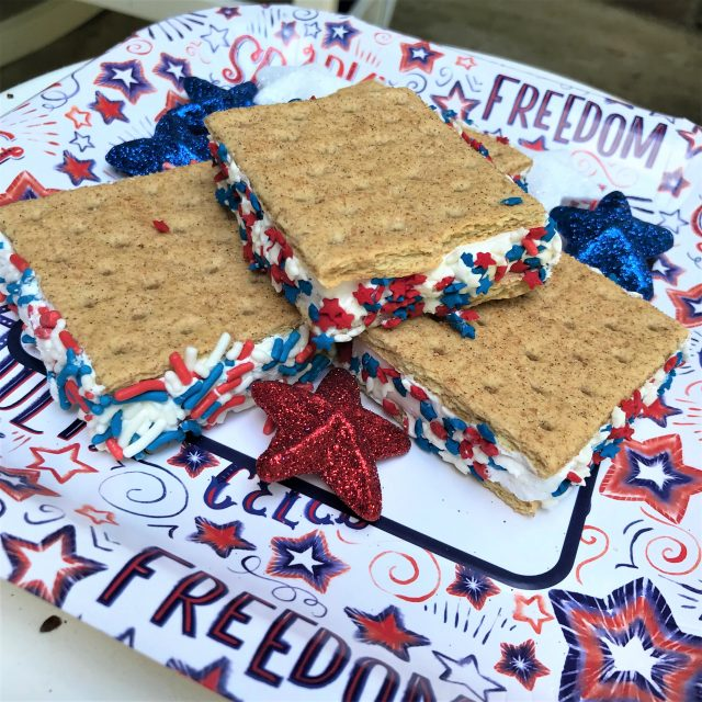 Close up red white blue frozen graham cracker sandwiches with sprinkles on patriotic paper plate