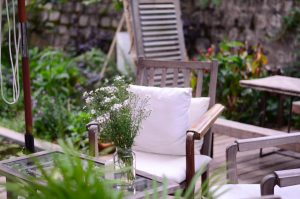 Wooden outdoor patio chair with white cushion with table and flowers in jar