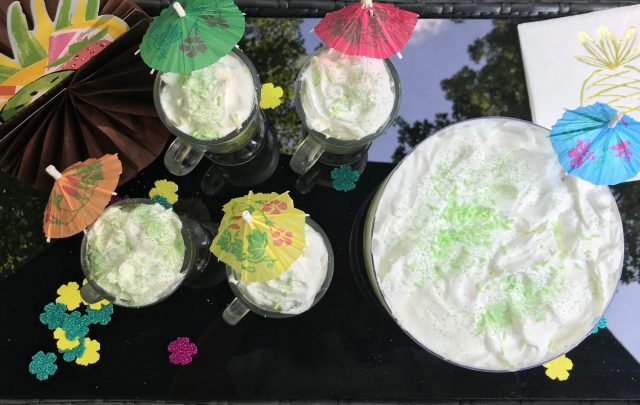 top view key lime coconut parfaits and trifles on table with drink umbrellas