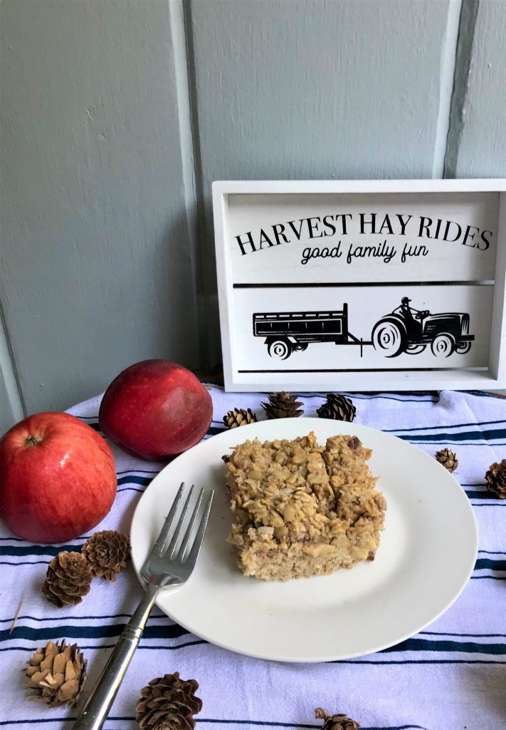 Slice of clean and healthy apple baked oatmeal on dish with apples and pine cones, refined sugar free, gluten free, and dairy free