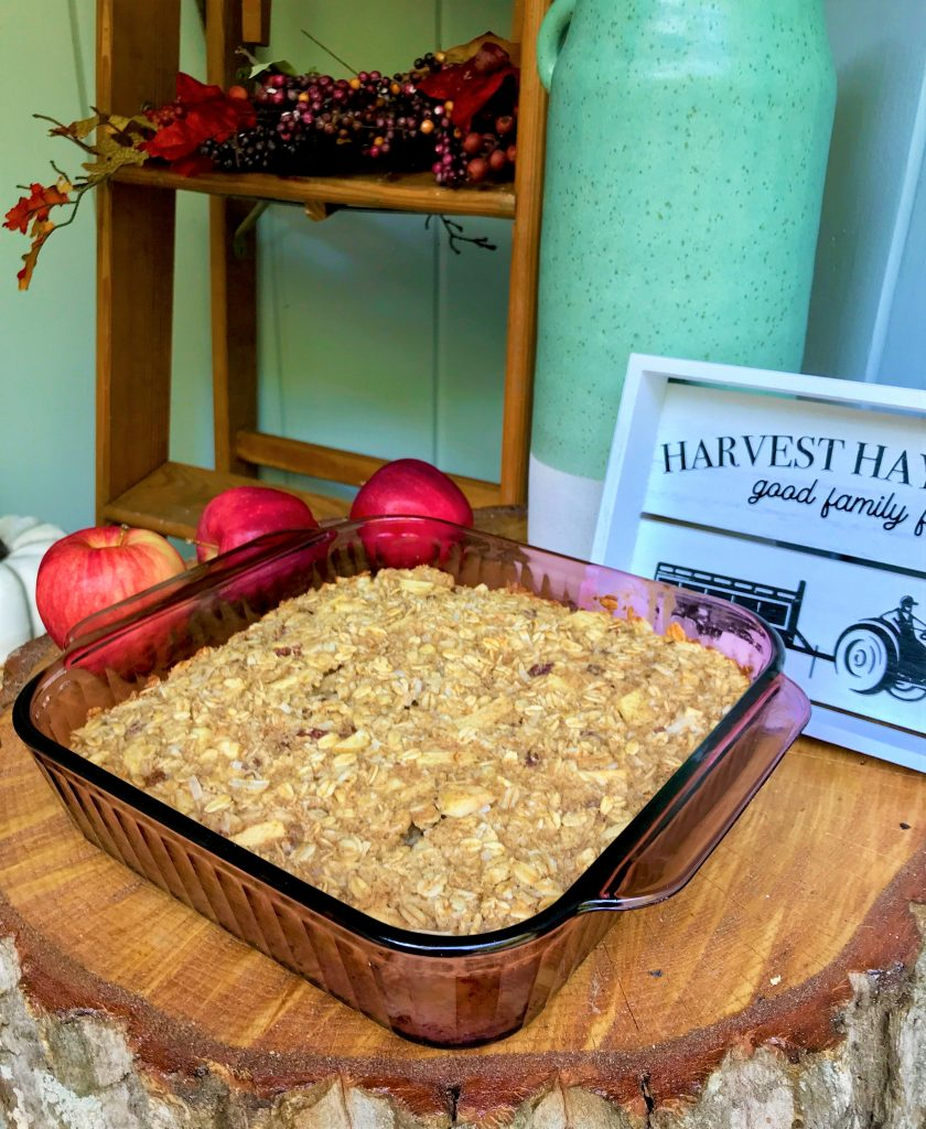 Close up of cooked clean and healthy apple baked oatmeal in baking dish with tree table with apples and fall decor
