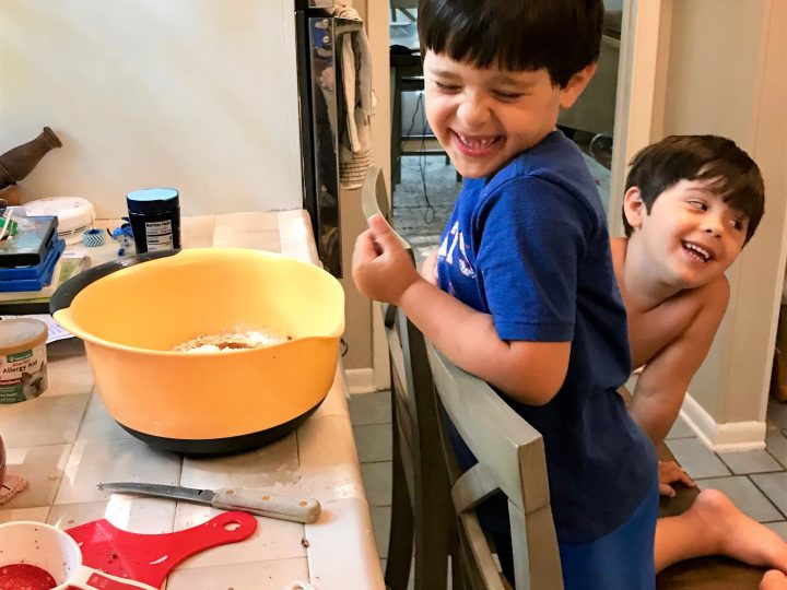 Little boys sitting at counter making healthy clean apple baked oatmeal