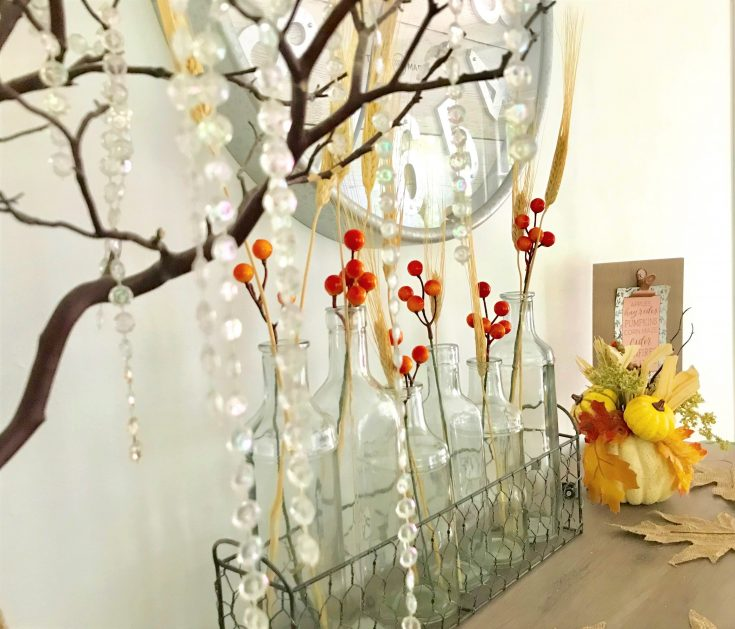 faux orange berries in glass jars with pumpkin and leaves spread, a simple way to decorate your home for fall on a budget