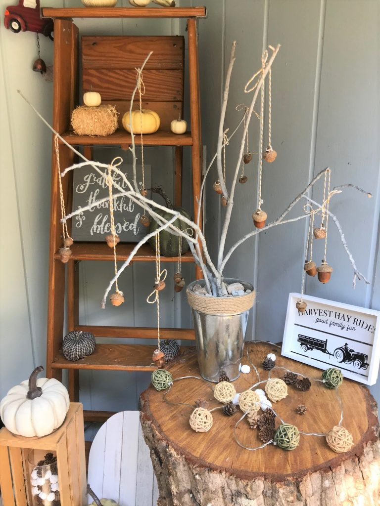 DIY acorn tree fall decor set on porch table with pumpkins and fall sign