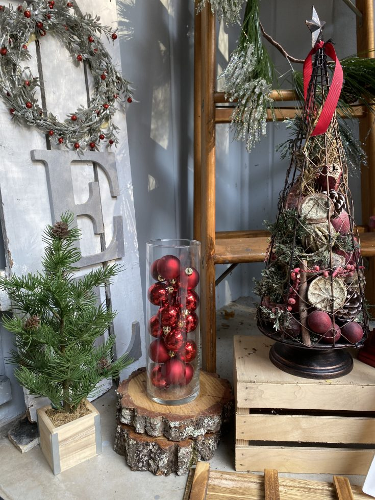 Rustic farmhouse porch with hurricane vase filled with red ornaments, picket fence NOEL sign, rustic wire Christmas tree - perfect easy and cheap Christmas decor idea!