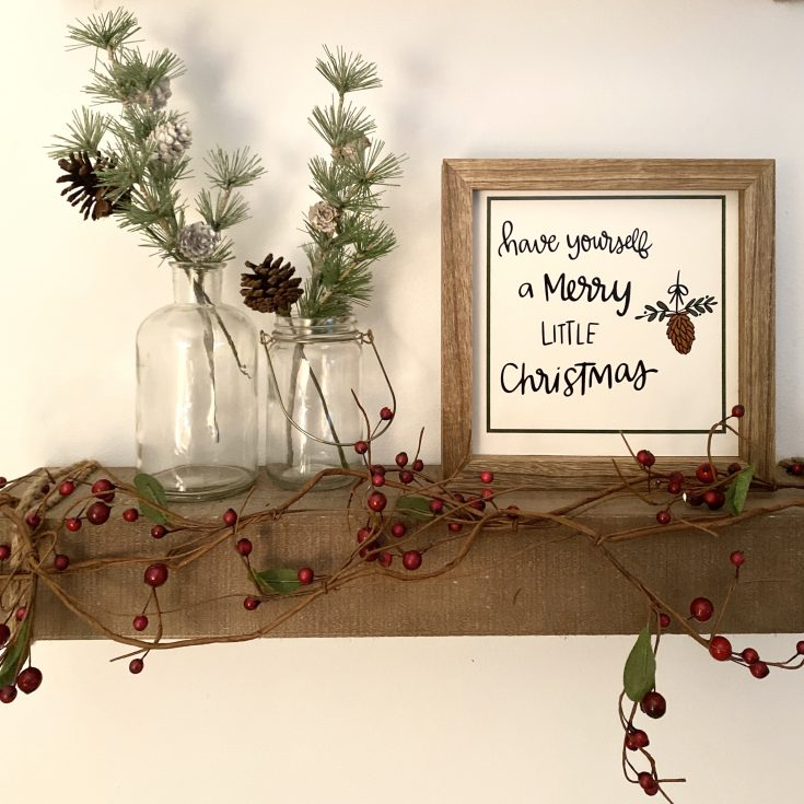 Styled farmhouse floating shelf decorated with glass bottle filled with flocked pines and pine cones, Have Yourself a Merry Little Christmas sign, and berry garland - perfect easy and cheap Christmas decor idea!