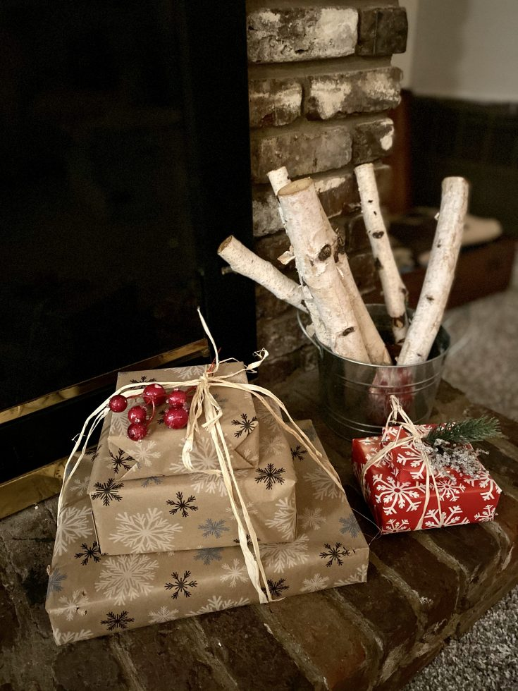 Rustic farmhouse galvanized bucket filled with birch logs with wrapped packages in snowflake butcher paper and raffia - perfect easy and cheap Christmas decor idea!